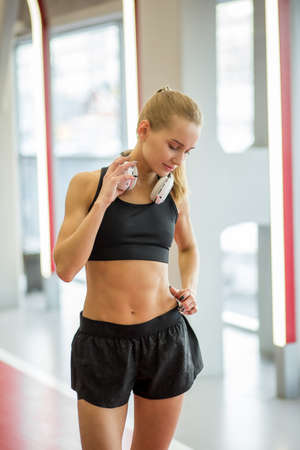 young blond woman standing in gym after workout Reklamní fotografie