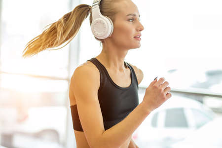 pretty young blond woman athlete with earphone running on track in gym