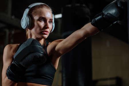 fighter girl wearing black sloses punching boxing bag in gym Foto de archivo