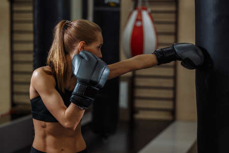 blond woman with boxing gloves, standing in position, ready to fight. Kickboxing and fight sport concept