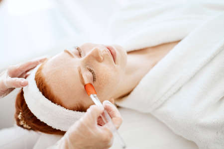 Face Skin Care. Unrecognizable beautician applying moisturising vitaminic gel on face using brush in spa salon. close up of female client receiving hydrating procedure in cosmetological clinic.