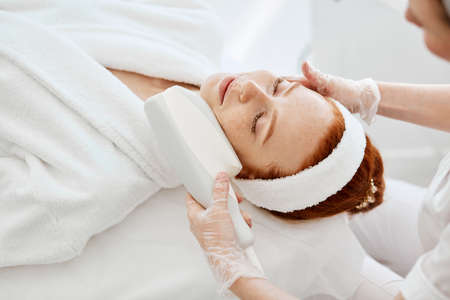 Hardware cosmetology. Top view of satisfied pleased young ginger woman with closed eyes receiving rf lifting procedure in a beauty parlour.