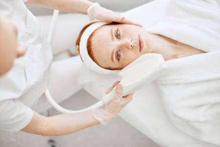 Cosmetology RF lifting equipment. Anti-age and anti-wrinkle apatherapy. Top view of beautiful woman in white bathrobe getting facial treatment and looking at camera at Cosmetology Salon. Stock Photo