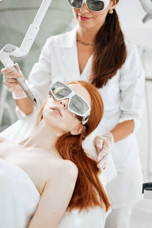 Specialists skilled in the laser skin resurfacing method making fractional laser resurfacing of the face of beautiful female client. Laser cosmetology concept.
