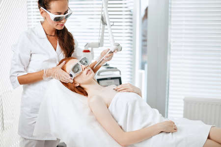 Well-groomed red haired woman undergoing laser resurfacing or smoothing which allows the patient to regain a youthful toned skin by scouring the facial lines.