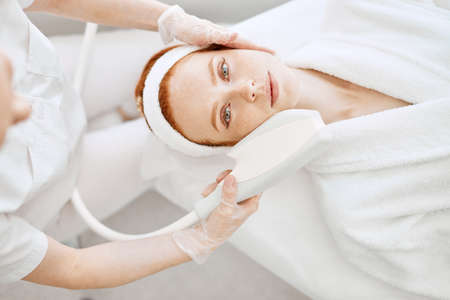 Why not pamper yourself with facial or body treatment. Attractive red haired woman with pefect freckled skin getting skin rejuvenation with RF lifting apparatus at professional beauty salon, top view