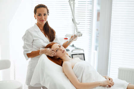Red-haired female patient receiving fractional resurfacing, a laser treatment suitable for those wanting a global anti-age treatment. Modern cosmetological trends and technologies.