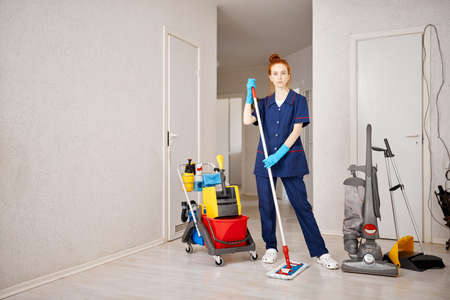 Portrait of young caucasian cleaning lady with redheaded attractive woman mopping hardwood foor at white room.