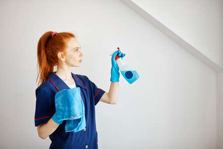 Beautiful red-haired housewife wearing household rubber gloves and blue dressing gown looking at camera posing with blue dusting cloth and wiper. Home cleaning concept.