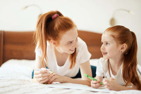 family, children and happy people concept - Close-up view of beautiful caucasian red-haired mother and daughter drawing a card for Daddy s b-day while lying on white bed, creative holydays with kids. Zdjęcie Seryjne
