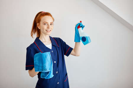 hotel maid dressed in professional blue uniform holding wiper and detergent prepares to clean room, having good mood isolated over white background. Smiling maid with cloth and detergent spray.