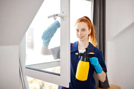 Smiling attractive hard working attractive room service housemaid in blue gown with red hair ponytail, cleaning a window with cleaning equipment. Standard-Bild