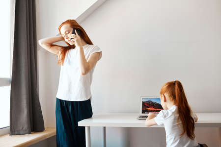 Education, entertainment and children concept. Young red haired teacher and cute girl with ginger hair using laptop for looking something, enjoying time together at home