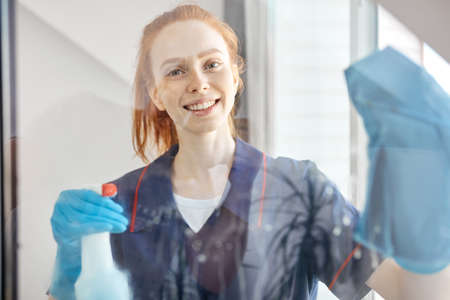 Portrait of red haired housemaid smiling through dirty windowpane , dressed in blue uniform holding sponge and detergent going to clean house windows.