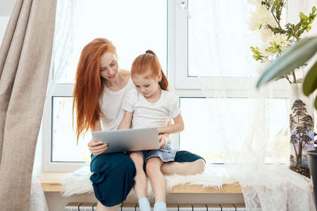 Relationship of mother and daughter concept. Red haired beautiful mom and little girl using laptop computer to play game togethers in weekend at home, sitting against big widow.