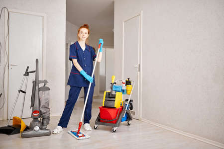 Pleased cheerful redhead maid woman holding mop pile, cleaning floor at vacant hotel room with cart of professional cleaning equipment on background. House cleaning service concept.