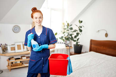Beautiful red-haired housewife wearing household rubber gloves and blue dressing gown looking at camera posing with red cleaning backet and wiper. Home cleaning concept.