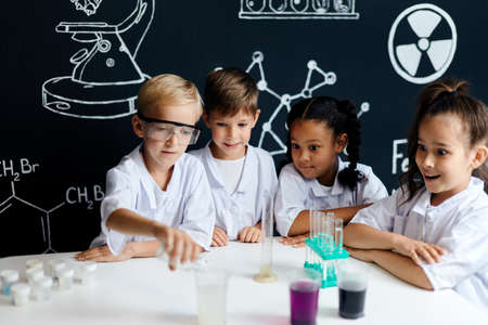 Curious adorable lovely kids studying chemical processes at elementary school, working on a group project while standing and watching reaction of liquid agent in test tubes Stock Photo