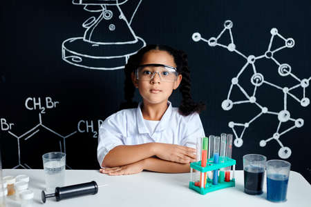 Adorable little Asian mixed race female scientist in protective googles standing against the blackboard . Children scientists making experiments in the laboratory. Educational concept.