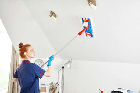 Beautiful red-haired young woman in blue working outfit using a mop while cleaning white ceiling in the white room.