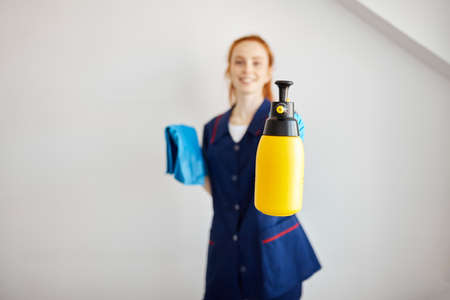 Happy hotel maid dressed in professional blue uniform holding wiper and detergent prepares to clean room, having good mood isolated over white background. Smiling maid with cloth and detergent spray.