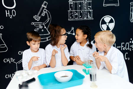 Group of multiracial diverse kids in scientist white clothes doing science experiments with reagents in the laboratory, being surprised and astonished with the results. Science and education in lab