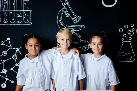 Multiracial group of diverse cute little children in white wear posing against black board with drawings at lab, two mixed race girls hugging a blonde caucasian boy and smiling at camera