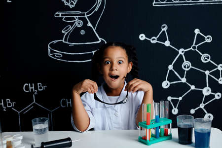 Mixed race asian little girl in scientist white clothes doing science experiments with reagents in the laboratory, being surprised and astonished with the results. Science and education in lab