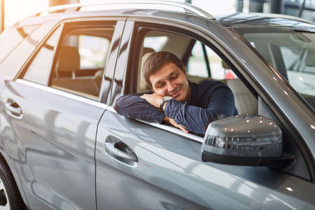 Visiting car dealership. Dreaming about new car salesman waiting for his clients and smiling, while sitting on driver place. Stock Photo