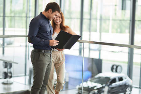 Good-looking caucasian couple reading car documentation in well-lit, airy car showroom.