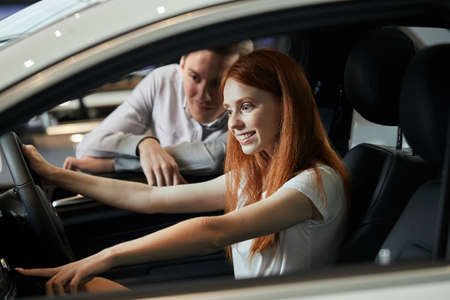 Cheerful younf female driver testing comfort of her new car in car showroom.