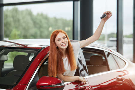 Happy excited ginger hair woman buying a new car. Female customer can not hide delight and admiration with her purchase and screaming loudly out of her car salon.