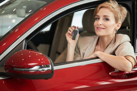 Cute pleased blonde business woman in a red car holding car key in her hand and looking at camera. Car Rent or Auto purchase Concept.