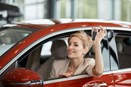Caucasian happy blonde woman in red luxury auto smiling at camera and showing new car key, ready for a road trip. Car Purchase or Rent concept