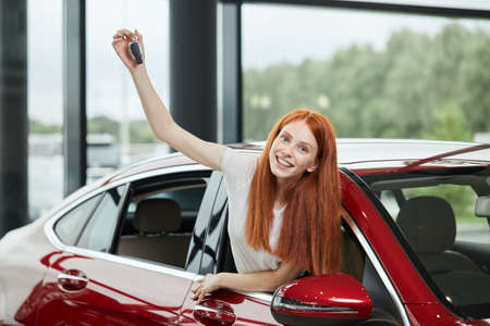 Car sale, consumerism and human emotions concept. Emotionally colored photo of overjoyed woman half sticking out from a car window screaming at camera, feeling herself the happiest woman at the world