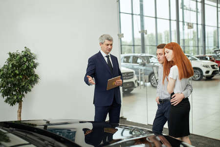 Sales agent at the table desk telling about car features to cheerful couple of customers at car dealership office Stockfoto