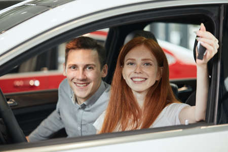 Young happy woman with red hair demonstrates the key of a new car at car showroom, gift from her husband, sitting beside.