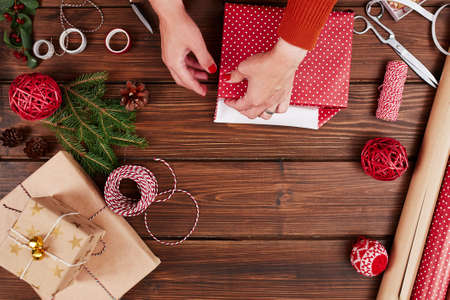 Woman s hands wrapping Christmas gift, close up. Unprepared Christmas presents on wooden background with decor elements and items, top view. Christmas or New year DIY packing Concept. 免版税图像