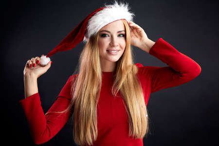 Happy long-haired blonde young female Santa Claus in Christmas hat and red elegant dress smiling at camera, waiting for your reaction, ready to celebrate New Year Party