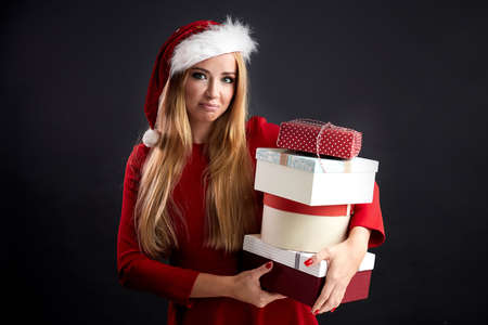 Unsatisfied or displeased blonde woman in Santa hat holding stack of Christmas gifts in her arms and looking at camera with disappointed look.