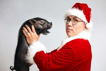 Father Christmas holding black little piggy in front of him looking at camera over white background with copy space.