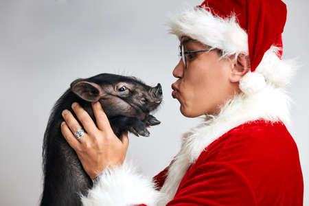 Profile shot of Asian Santa Claus in Christmas suit and spectacles holding little black pig planning to kiss it, isolated over white background