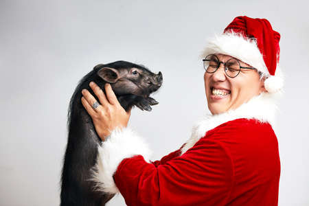 Profile shot of happy Asian Santa Claus in Christmas suit and spectacles holding little black mini pig with closed eyes, isolated over white background with copy space.