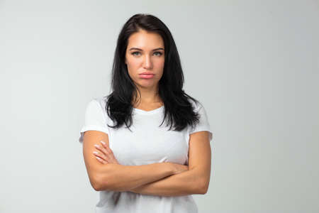 disappointed woman standing with arms crossed and expressing resentment isolated over white background. close up photo.emotions concept, bad mood. copy space