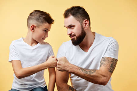 smiling father and son with pleasant smile give fist bump to each other Stock Photo
