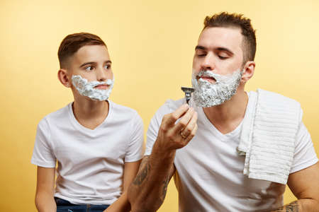 bearded Father and son shaving on yellow background