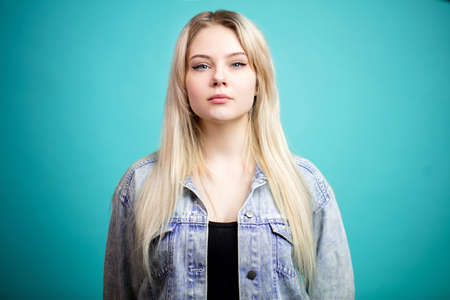 Pleasant blonde young woman looking at camera with serious face expression over blue background. 版權商用圖片