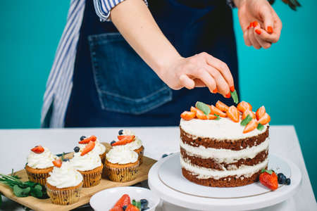 Cropped image of woman hands decorating cupcakes with strawberries.
