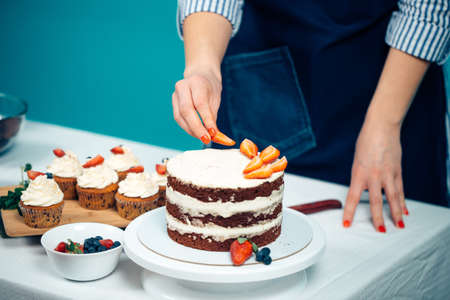 Cropped view of woman hands decorating cupcakes with summer fresh berries
