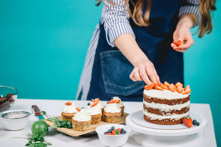 Cropped view of womans hands putting strawberries on cake 免版税图像